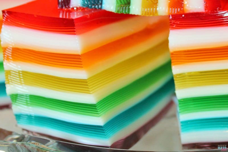 This rainbow jello is stunning and while it looks difficult to make, it's easy! These are easy to follow step-by-step directions! Perfect for your next rainbow party or holiday gathering!