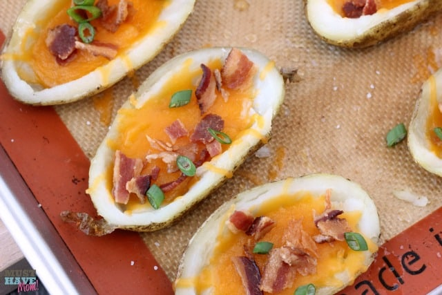 Homemade potato skins with cheddar and bacon. Perfect game day food, appetizer or side dish! These are so delicious they never last long at my house!