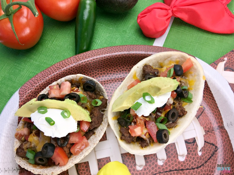 These Mexican Pizza Taco Boats are perfect game day food! Think Mexican Pizza recipe converted into a portable, mess-free tortilla boat! Eat these while you watch the big game or make them for dinner!