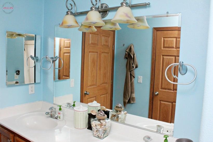 Builder grade bathroom mirror makeover. How to make a DIY bathroom mirror frame.