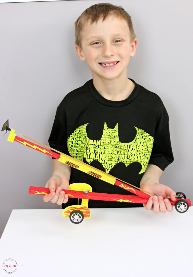 boy holding young woodworkers kit club turbo racer project