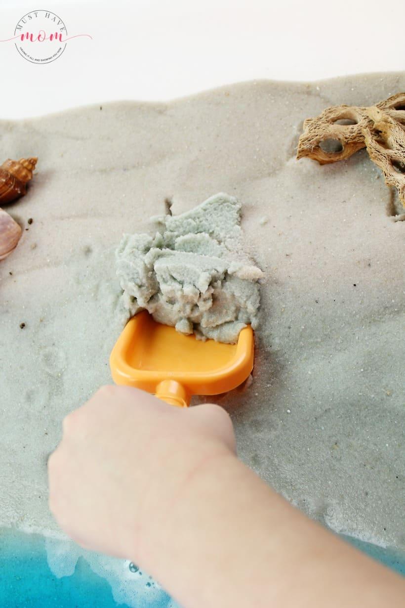 scooping sand in sensory bin
