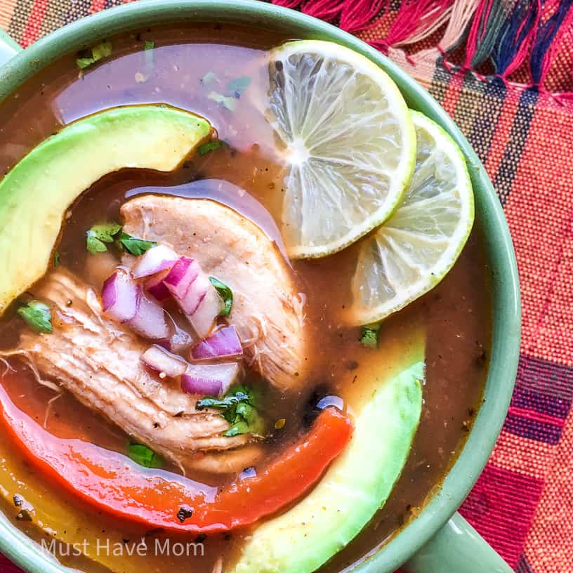 chicken fajita soup in a bowl with avocado, limes and garnish