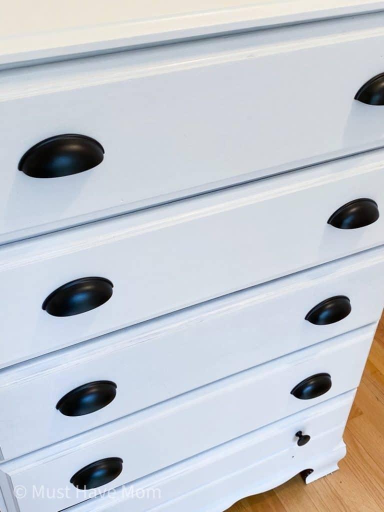 black hardware on white dresser